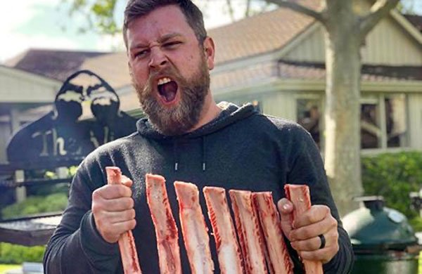 Derek Wolf holding a rack of raw ribs