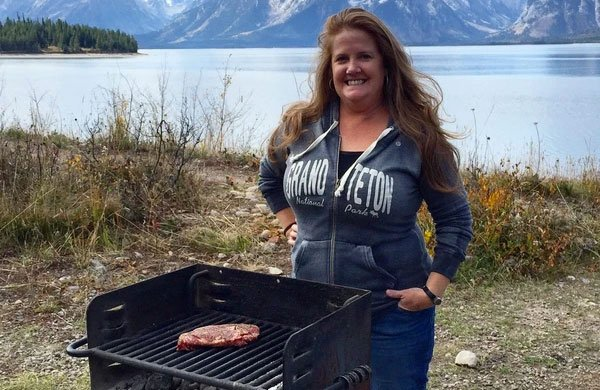 Christie Vanover outside cooking on a grill