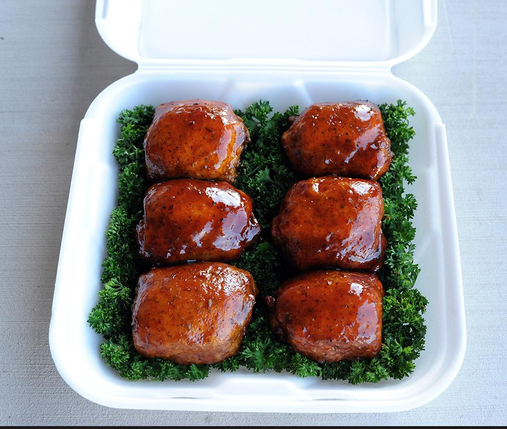Christie Vanover chicken thighs in a container on a bed of lettuce