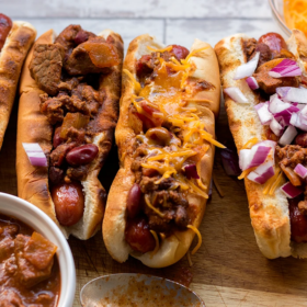 Cowboy chili dogs lined up topped with onion and cheddar cheese