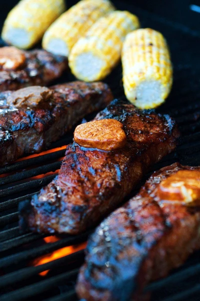 New York steak with corn on the cob on the grill