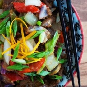 Spicy orange beef with fresh veggies in a bowl