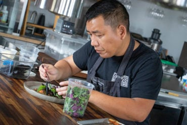 Chef plating microgreens on a dish