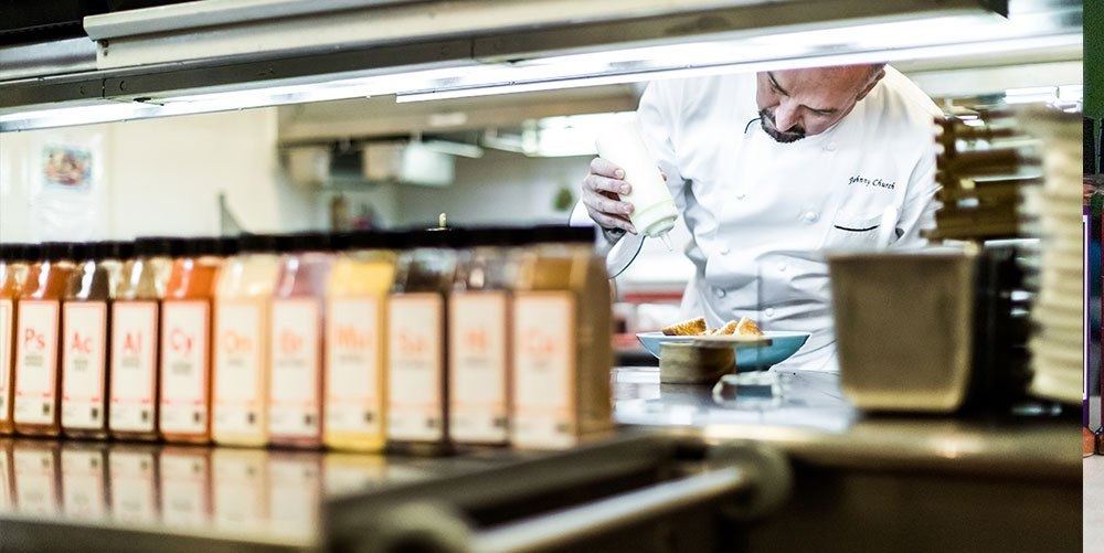 Chef in the kitchen plating a dish with spices in backdrop