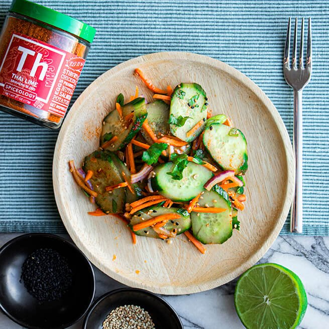 a wood plate with Thai Lime Sriracha Cucumber salad on it