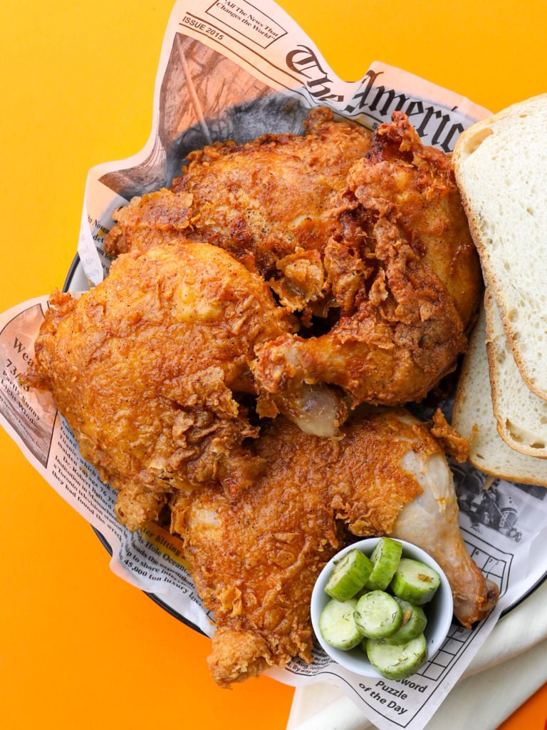 a plate of nashville hot fried chicken with pickles and white bread