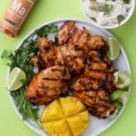 a plate of grilled mango chicken on a white plate with green background