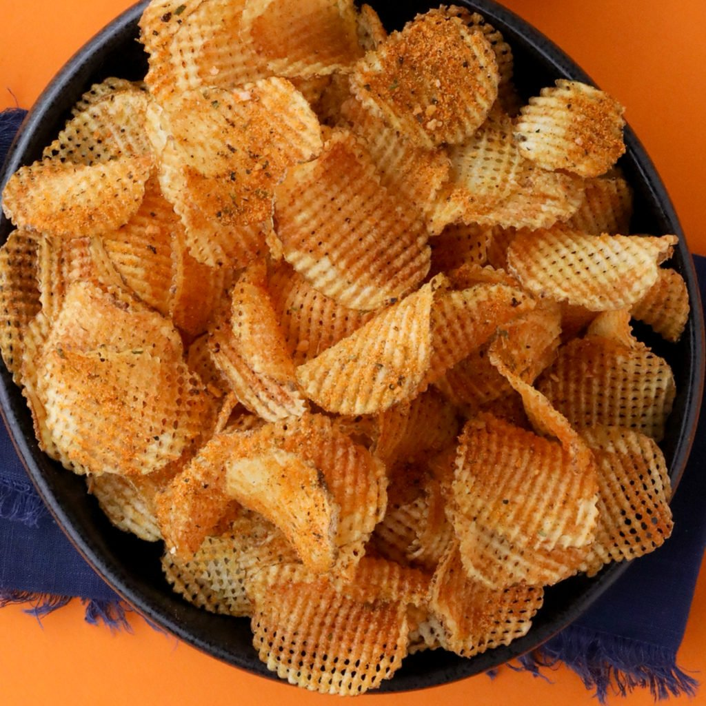 a bowl of waffle chips on an orange background