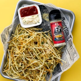 a sheet pan of shoestring french fries on a yellow background
