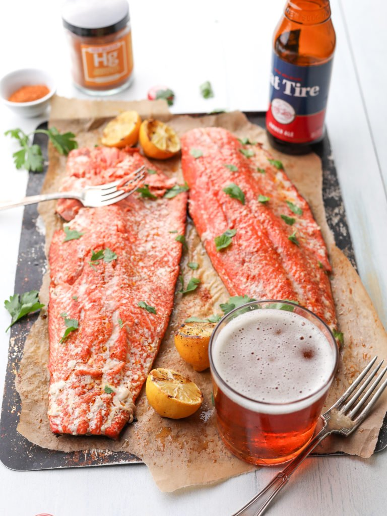2 salmon fillets on brown parchment with a glass of beer and a jar of spices. habanero grapefruit grilled salmon