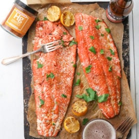 2 salmon fillets on parchment with a jar of spice, bottle of beer and glass of beer