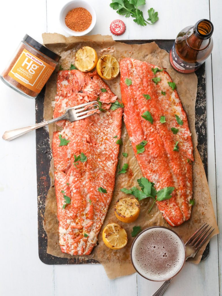 2 salmon fillets on parchment with a jar of spice, bottle of beer and a glass of beer