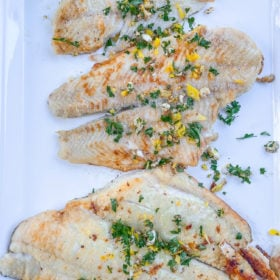 a white platter with petrale sole fillets and a parsley gremolata on top