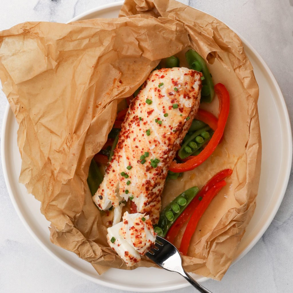 cooked halibut over vegetables on a white plate
