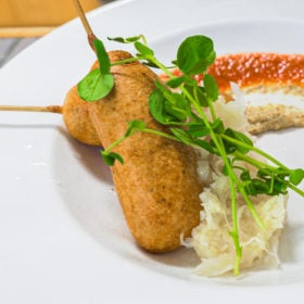 Bratwurst corn dogs on plate with tomato jam, sauerkraut and sprouts