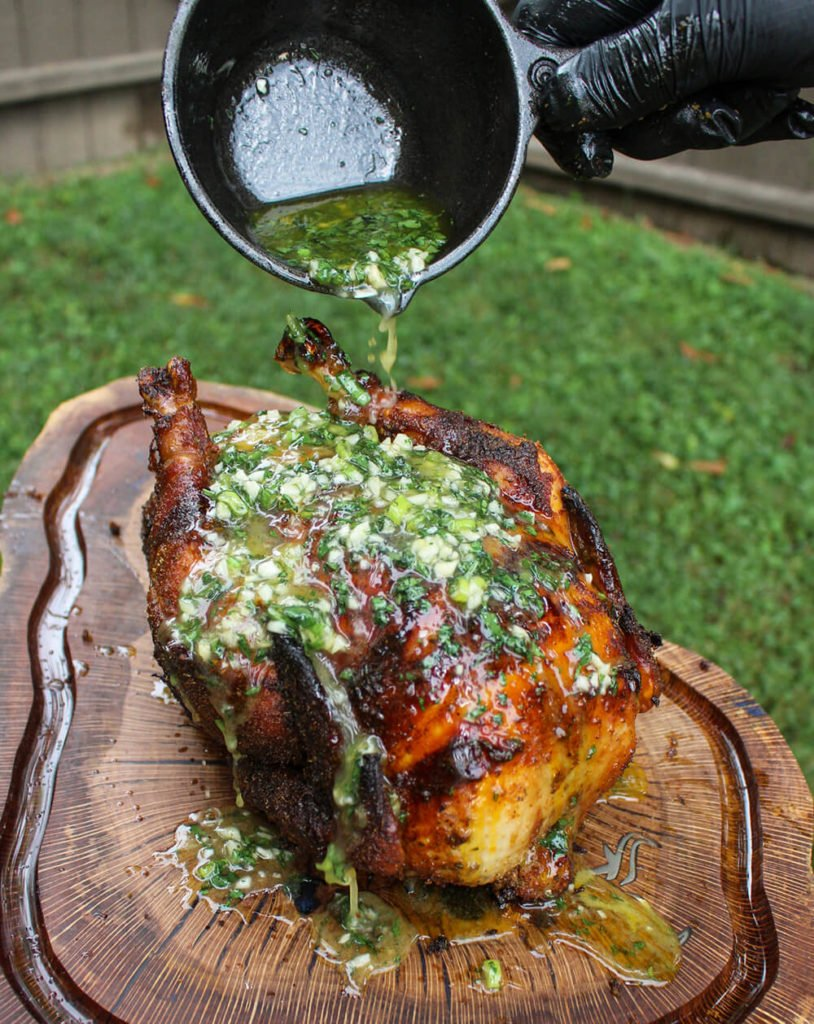 lemon chili rye rotisserie chicken cutting board with butter sauce pouring on top