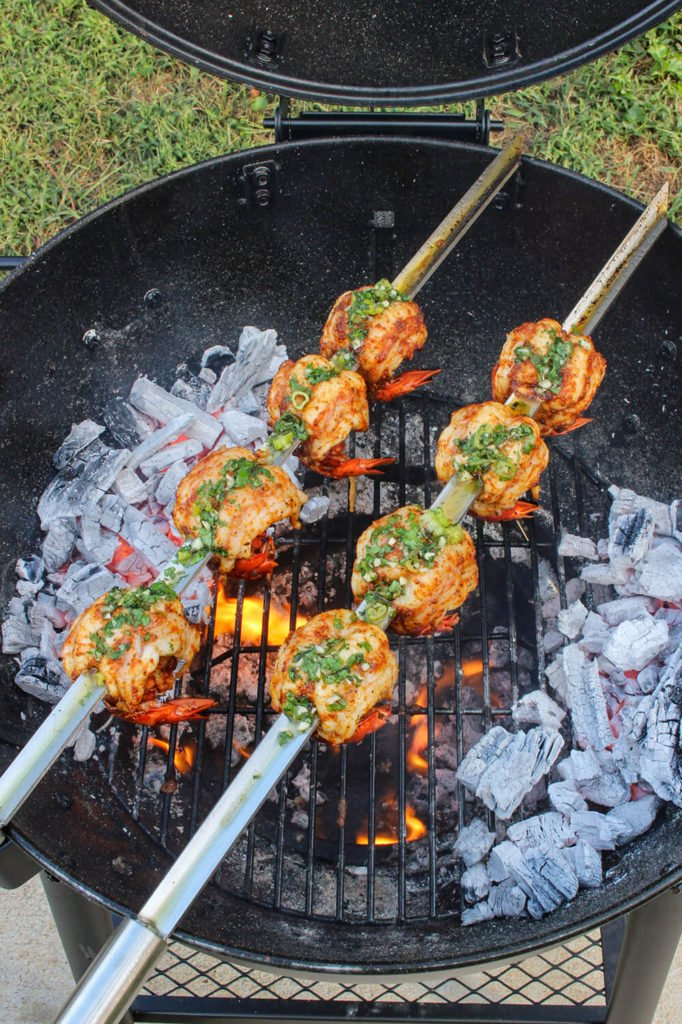 Smoked chipotle mexcal lobster tails skewers over grill