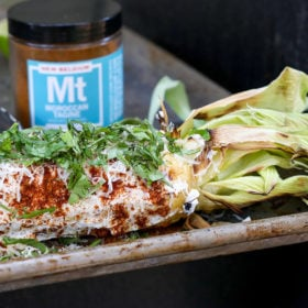 Moroccan tagine street corn on tray with spice jar