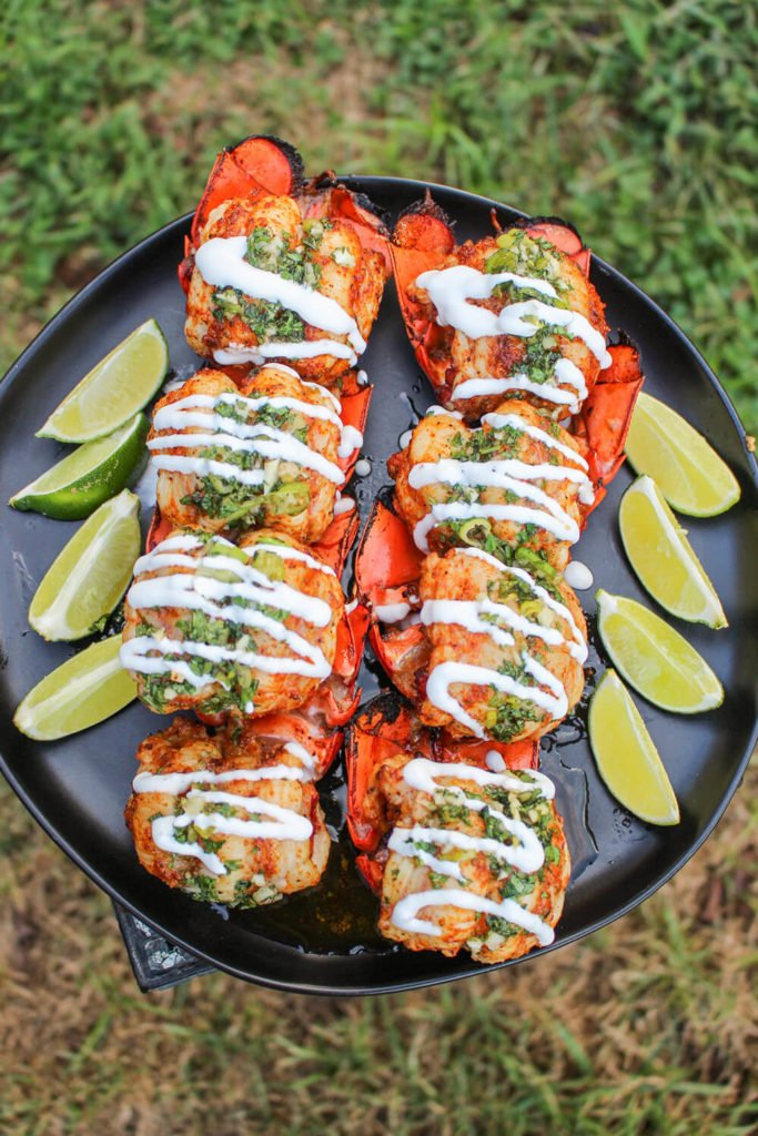 smoked chipotle mezcal lobster tail skewers on plate with lime wedges