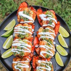 Smoked chipotle mezcal lobster tails on plate with lime wedges