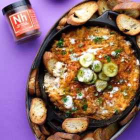 A tray of nashville hot chicken dip with bread and pickles on a purple background
