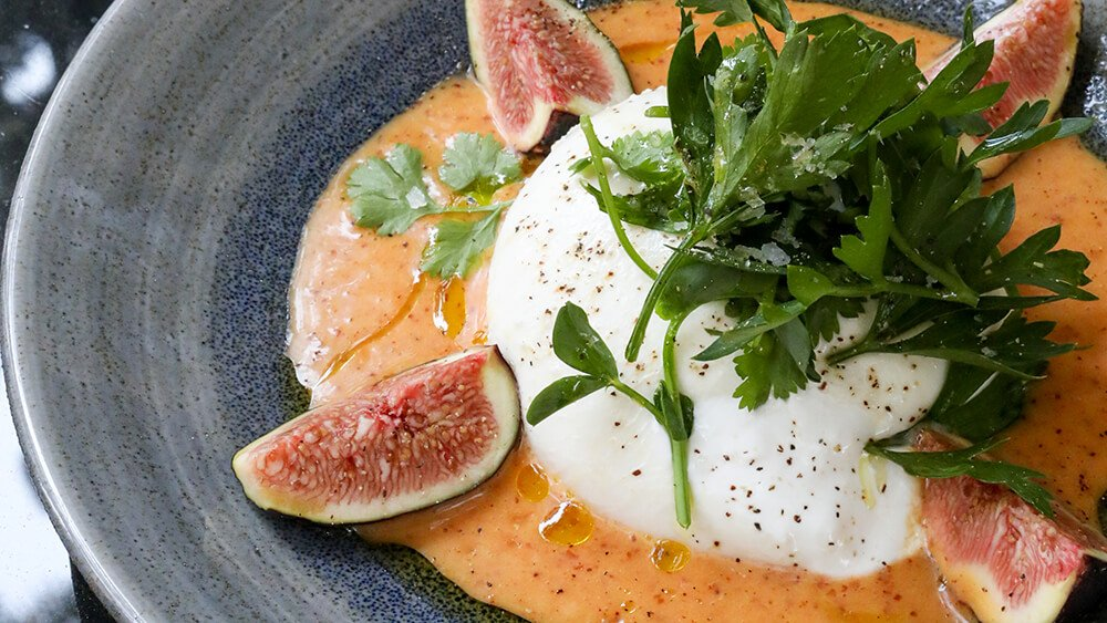 Habanero grapefruit vinaigrette with burrata and figs topped with greens