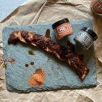 Pork loin honey habanero glaze sliced on board with spice jars